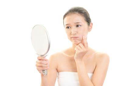顔のシミを気にする女性